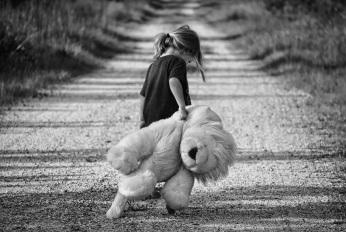 Gender neutral kid - boy or girl - with teddy bear